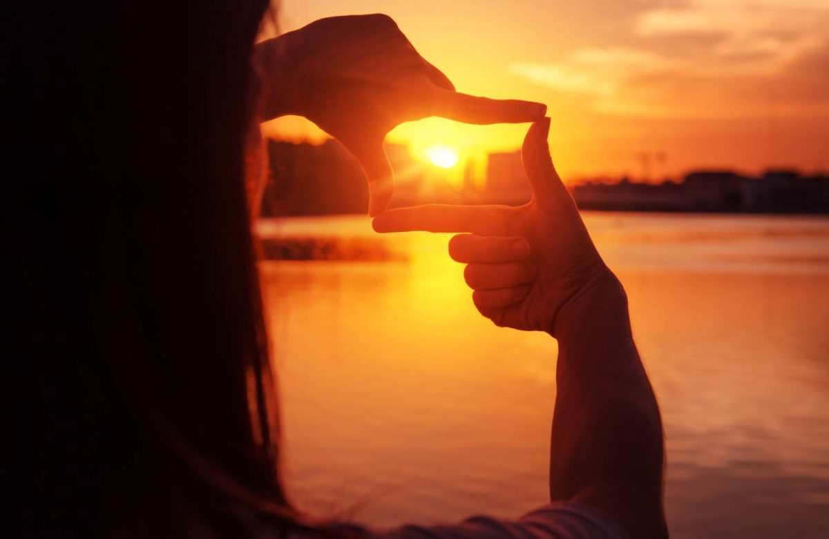 Woman hands making frame gesture with sunset.